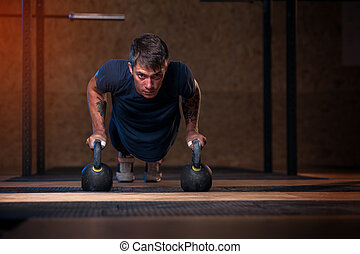 Young muscular man training with kettle bell