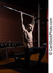 Young muscular man with a barbell bar in gym