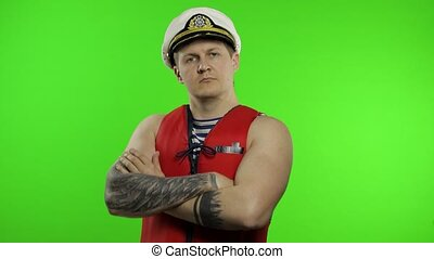 Young muscular sailor man works as lifeguard at beach arms crossed, looking at camera. Seaman guy life saver in sailor's vest, lifejacket, captain nautical hat. Isolated on chroma key background