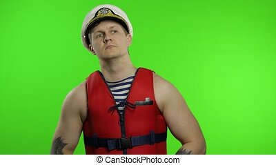 Young muscular sailor man works as lifeguard at beach observe the territory. Seaman guy life saver in sailor's vest, lifejacket, captain nautical hat. Isolated on chroma key background. Green screen