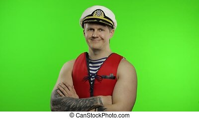 Young muscular sailor man works as lifeguard at beach show thumbs up and looking at camera. Seaman guy life saver in sailor's vest, lifejacket, captain nautical hat. Isolated on chroma key background