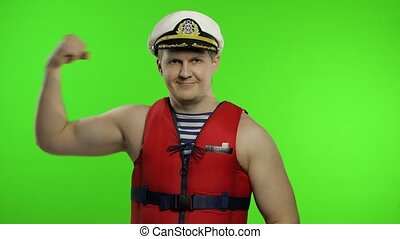 Young muscular sailor man works as lifeguard at beach shows muscles, looking at camera. Seaman guy life saver in sailor's vest, lifejacket, captain nautical hat. Isolated on chroma key background