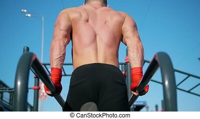 Young muscular sportsman pushing up at the parallel bars - workout at summer outdoor - rear view