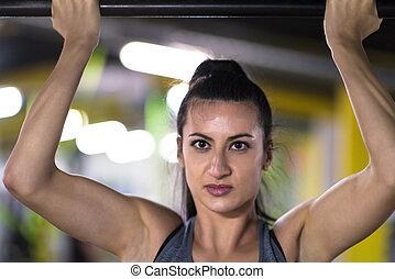 woman doing pull ups on the horizontal bar