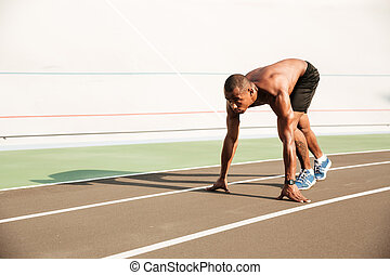 Young musculary african sports man in starting position ready to start