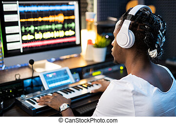 Young musician in headphones looking at sound waveforms on ...
