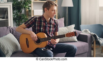 Young musician is tuning acoustic guitar touching strings...