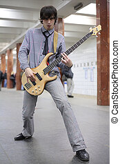 young musician play on guitar at metro station