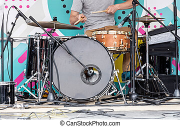 young musician playing drums on outdoor stage during the music fest
