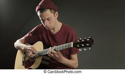 Young musician playing guitar in dark studio