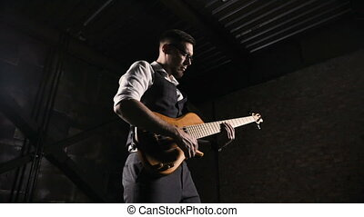 Young musician playing on guitar in loft studio - Rock...