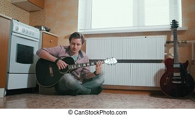 Young musician plays the guitar sitting on the floor in the kitchen