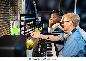 Young musicians looking at computer screen during discussion...