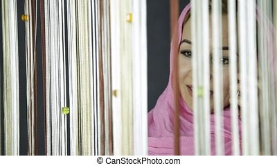 young muslim arabian woman in pink hijab looking out the window and waving his hand to friends