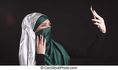 Young Muslim Girl in Hijab Doing Selfie on Mobile Phone Camera.