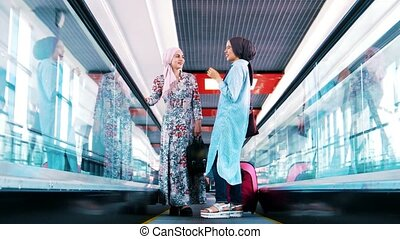 Young muslim girl riding the escalator, talking and...