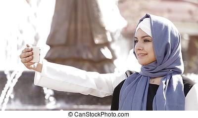 Young Muslim Girl Uses Smartphone.