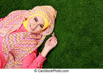 Young muslim girl wearing hijab lying on grass with copy...