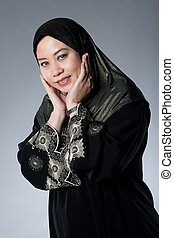 Young Muslim Malay woman in black hijab with hands over her...