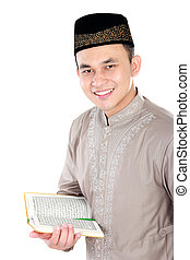 young muslim man holding the Quran - portrait of handsome...
