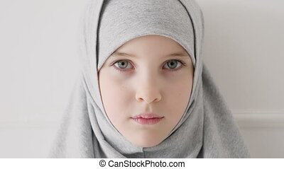 Young muslim teen girl in hijab shyly looking at camera and...