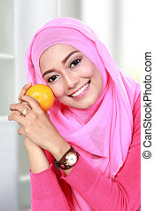 young muslim woman hold an orange