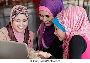 young muslim woman in head scarf using laptop in cafe with friends