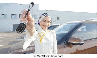 Muslim woman in hijab with car key outdoors