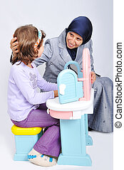 Young muslim woman playing and learning little daughter