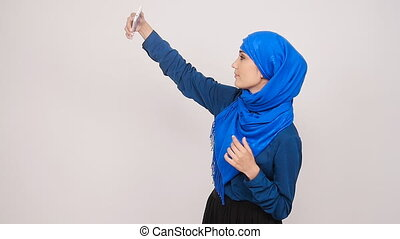 Young muslim woman posing taking selfie photo with...
