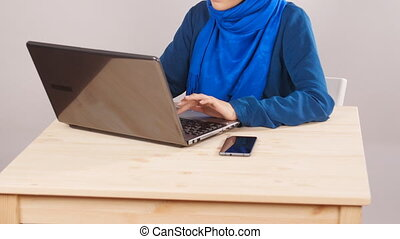 Young Muslim woman sitting in office and working on laptop...