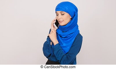 Young Muslim woman talking on cell phone