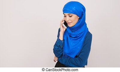Young Muslim woman talking on cell phone - Muslim woman...