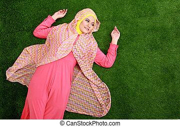 Young muslim woman wearing hijab lying on grass
