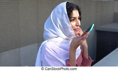 Young Muslim woman wearing hijab texting message with her ...
