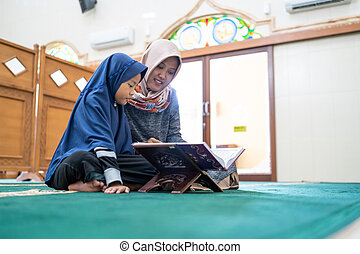muslim woman with kids reading quran together - young muslim...