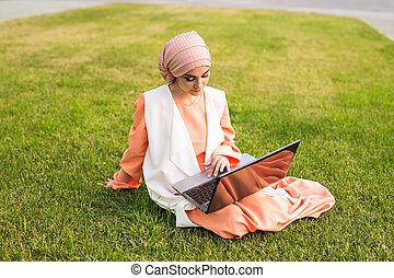 Young Muslim woman with laptop in the park