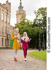 Young muslim women walking to university together