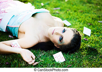 Young mysterious woman with cards in the grass