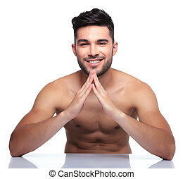 young naked beauty man making a house with his hands