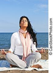 Portrait of beautiful native american girl doing yoga at beach