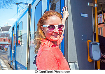 Young native dutch woman getting on the tram in Amsterdam the Netherlands