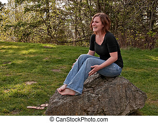 Young Natural Looking Woman Laughin While Sitting on Rock Barefo