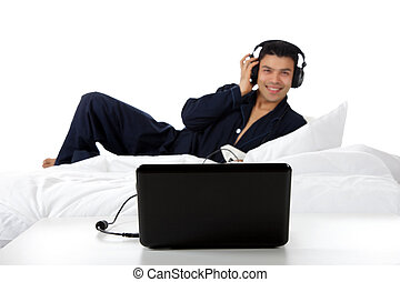 Young nepalese man in pajamas, laptop.
