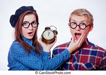 Young nerd couple holding alarm clock