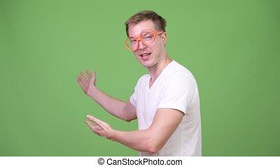 Young nerd man talking while showing something - Studio shot...
