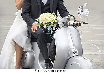 Young newlywed just married, posing on an old gray scooter