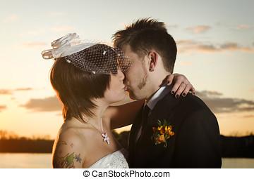 Young newlyweds kissing along riverbank at sunset
