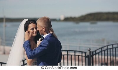 Young newlyweds standing in the quay in day of their wedding ceremony. Beautiful bride and groom enjoying each other.