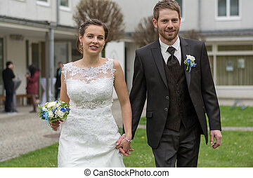 Young newlyweds walking in the park - junges Hochzeitpaar...
